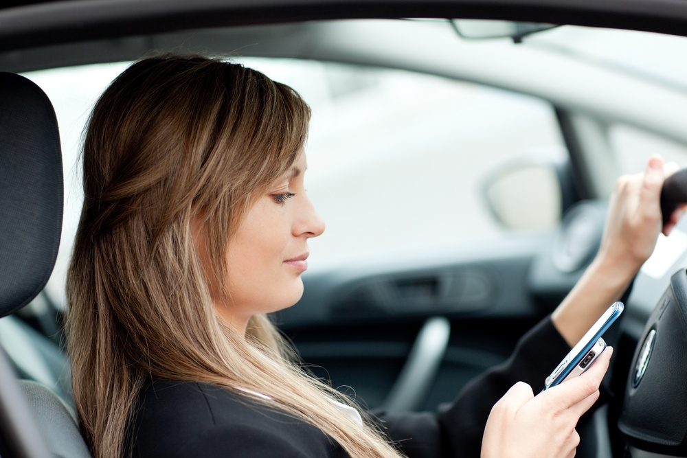 businesswoman sending a text while driving to work