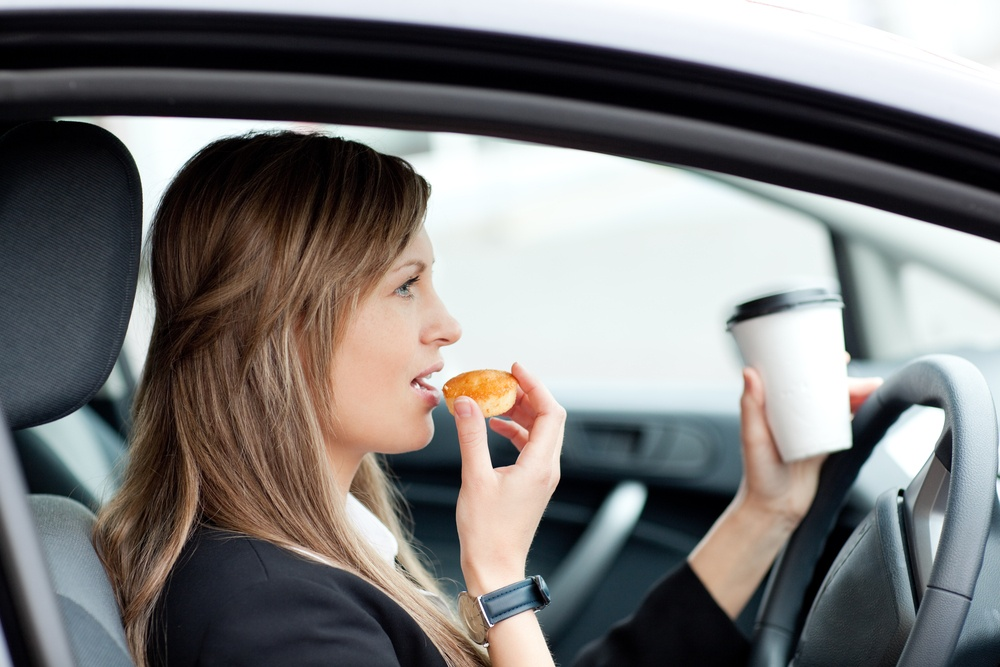 businesswoman eating and holding a drinking cup while driving to work what are the three types of distracted driving distracted driving