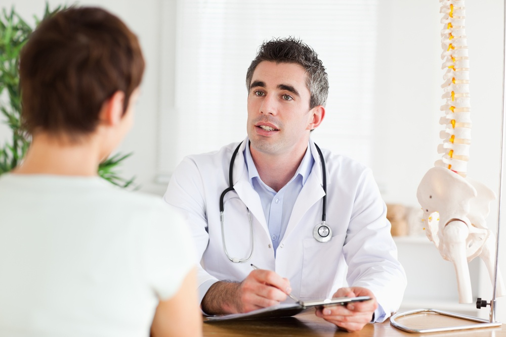 Male Doctor writing something down while patient is talking in a room.jpeg