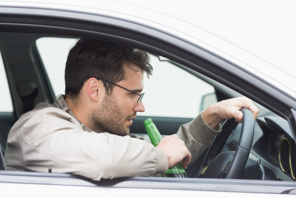 Man drinking beer while driving in his car.jpeg