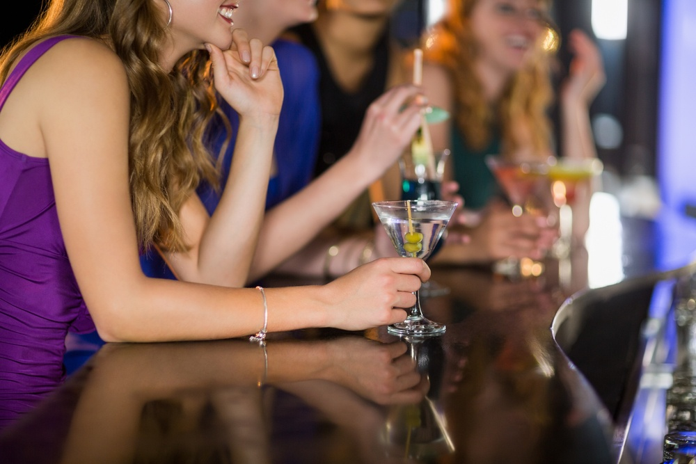 Mid section of smiling woman having glass of cocktail in bar