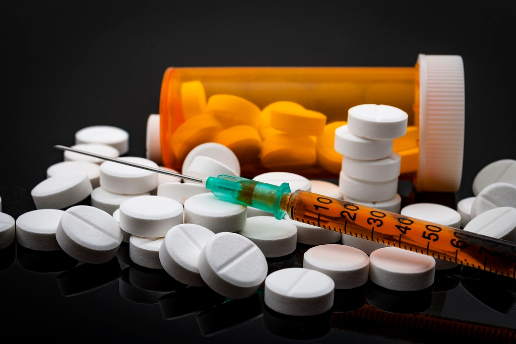 Scattered pills in front of a pill bottle and an injection needle