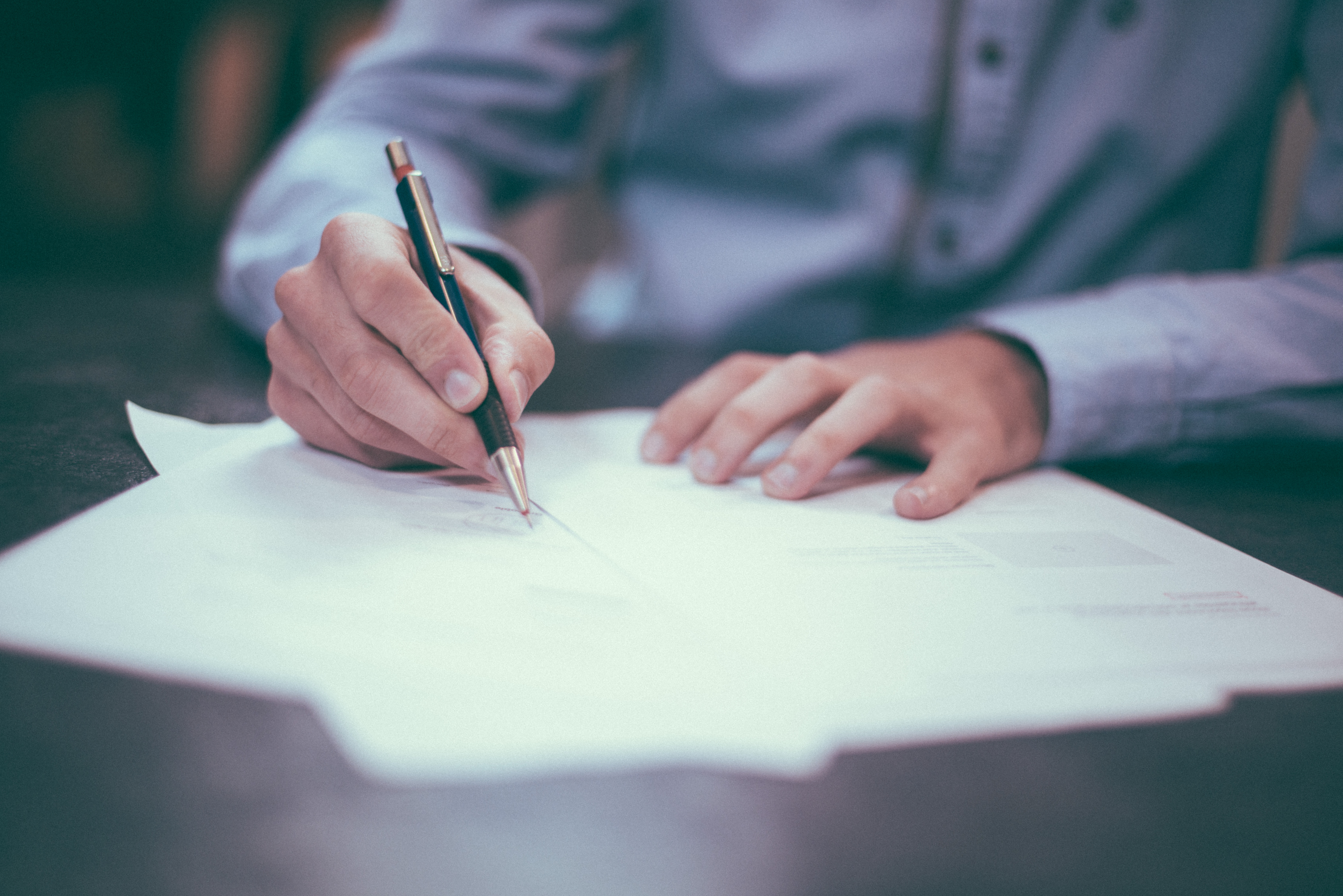Man in a shirt signing some papers