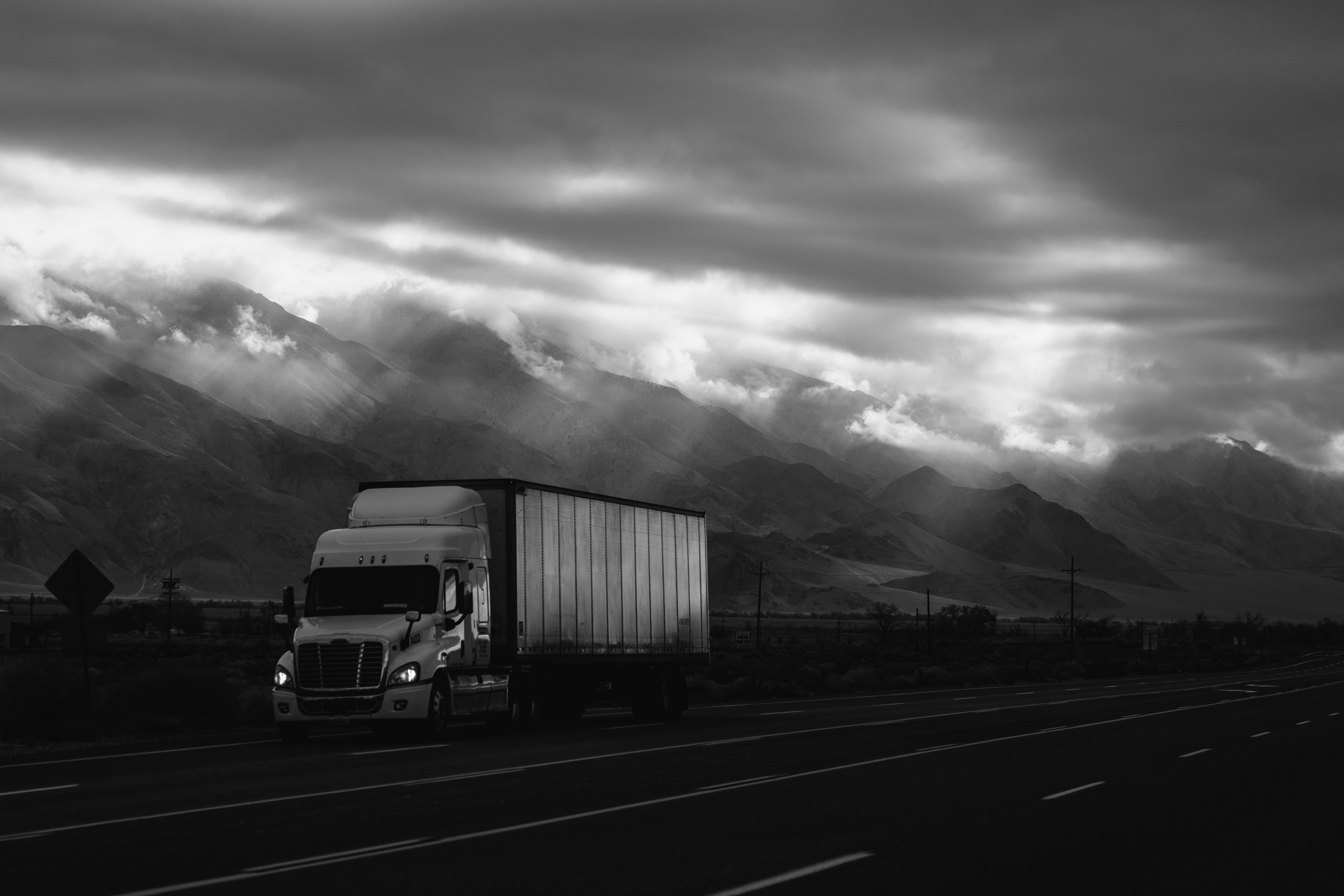 Black and white image of a truck driving