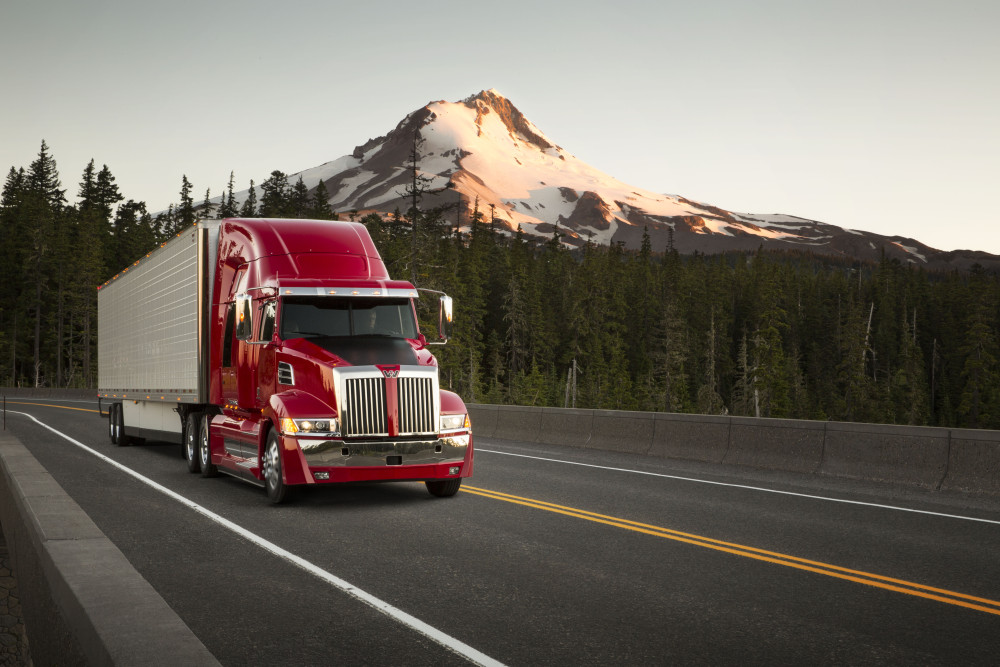 Truck driving on a road with a mountain in the background
