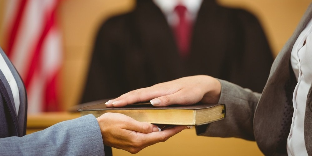 Witness swearing on the bible telling the truth in the court room