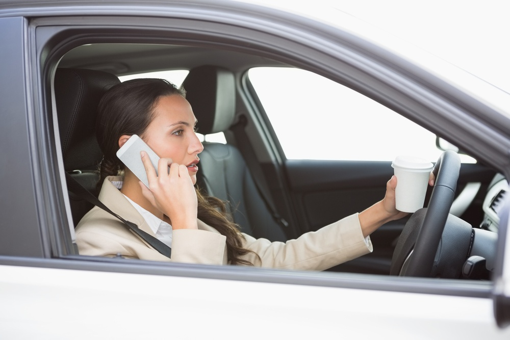 are tougher laws needed to combat distracted driving women in car on phone holding a coffee