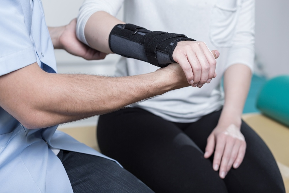Woman using wrist immobiliser after hand injury
