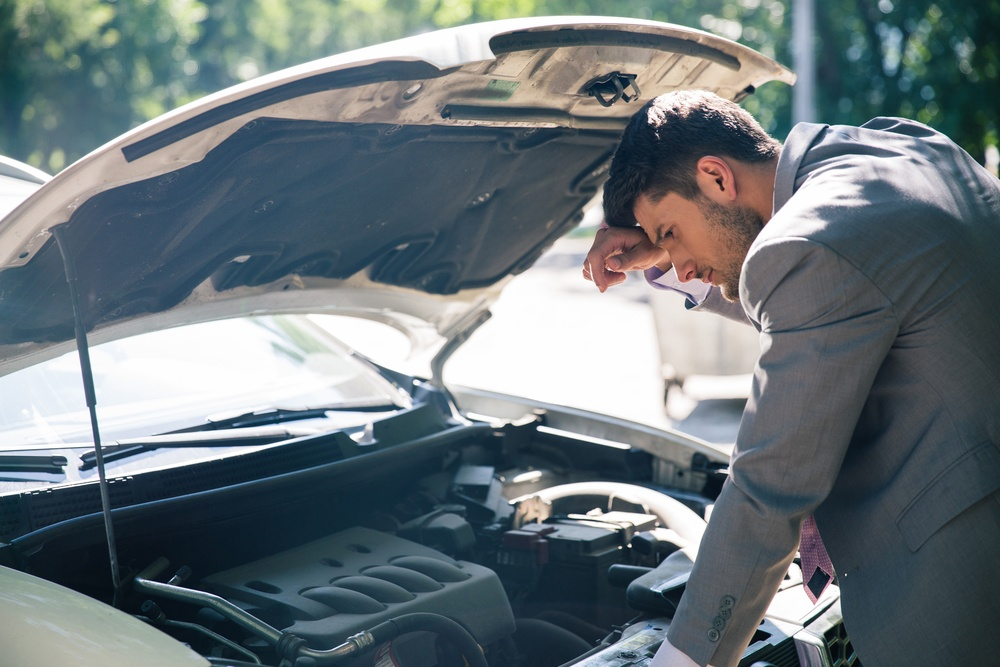 man checking under the hood of his car after a car accidents things you should never say to your insurance company after an accident