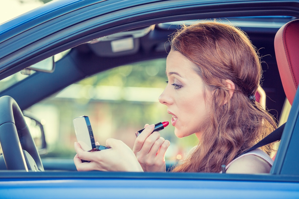 Young woman applying makeup while driving car what are the consequences of distracted driving distraced driving