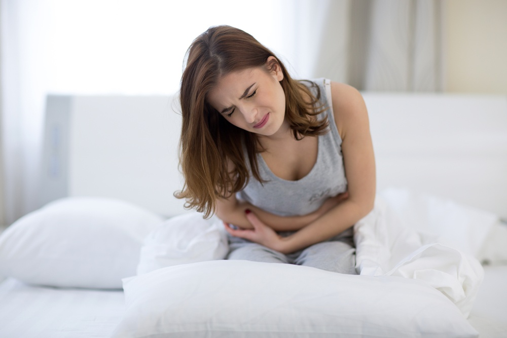 woman sitting on the bed with pain